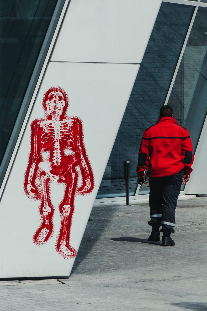 man walking past graffiti of skeleton on wall