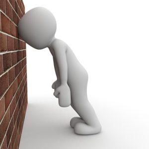 壁にうな垂れる人間